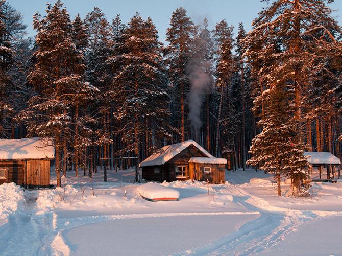 избушки на берегу озера в Карелии зимой
