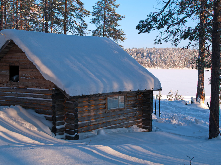 Изба Хирмуш зимой на берегу озера в Карелии